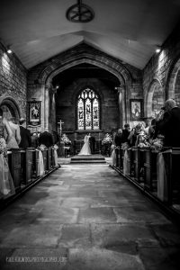 Black and white photo of bride and groom standing at the end of a long church aisle getting married